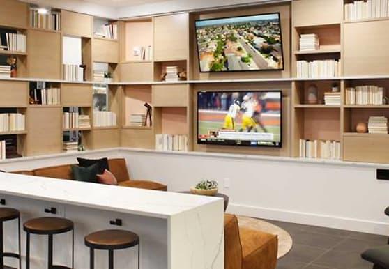 kitchen featuring a breakfast bar, TV, dark tile flooring, light countertops, and white cabinetry, Avalon Meydenbauer