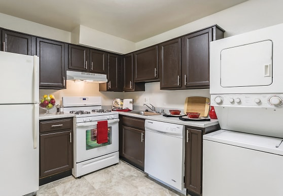 kitchen with ventilation hood, gas range oven, dishwasher, washer / dryer, refrigerator, dark brown cabinetry, light countertops, and light tile flooring, The Apartments at Bonnie Ridge