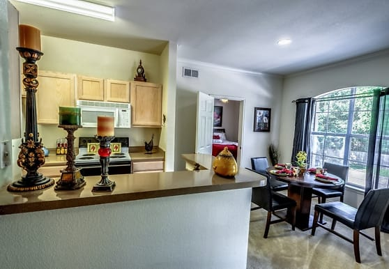 kitchen with carpet, natural light, electric cooktop, microwave, light floors, dark countertops, and light brown cabinets, Audubon Lake Apartment Homes