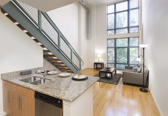kitchen with natural light, stainless steel dishwasher, brown cabinetry, light stone countertops, and light hardwood flooring, Delancey at Shirlington Village
