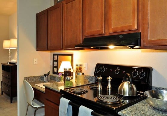kitchen featuring range hood, dark brown cabinetry, and light flooring, Stockwell Landing