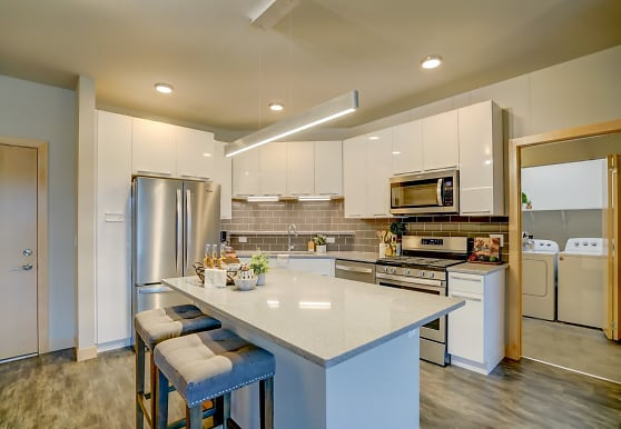kitchen featuring a center island, a kitchen breakfast bar, stainless steel appliances, gas range oven, independent washer and dryer, white cabinetry, pendant lighting, light parquet floors, and light countertops, Latitude 43