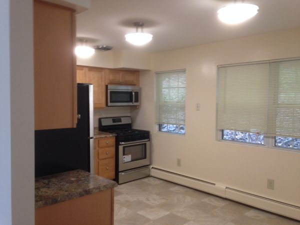 kitchen featuring stainless steel microwave, range oven, baseboard radiator, dark stone countertops, light tile flooring, and brown cabinetry